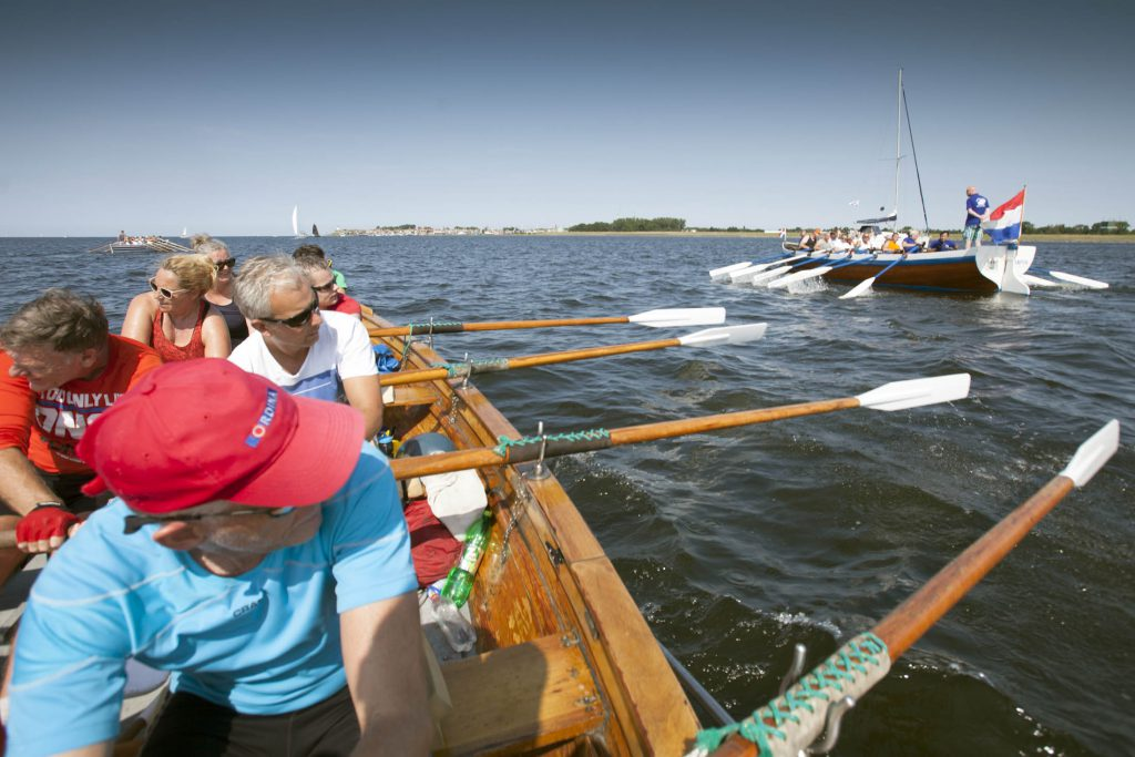 27-8-2016 Urk, sloeproeiers uit de regio sluiten inmiddels traditioneel het vakantie seizoen af met een stevige roeitocht. Vandaag roeien 44 roeiers en enkele stuurlieden uit Emmeloord, Harderwijk, Urk, Deventer, Kampen, Hattem en Zwolle met vier roeisloepen an KAmpen naar Urk. De tocht over het ijsselmeer, ketelmeer en ijssel duurde zo'n drieenhalf uur. Op de foto roeien drie sloepen op het ijsselmeer met het uitzicht op het vml Eiland Urk. in de verte roeiploeg Urk, rechts roeisloep 'Stad Kampen' en op de voorgrond de roeiers in de Isela